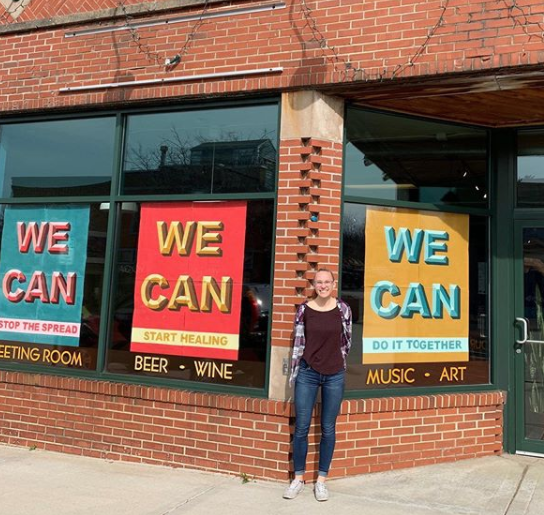 Maddie LeBrun '20 stands outside a shop in Oregon, WI that displays her posters in the windows.